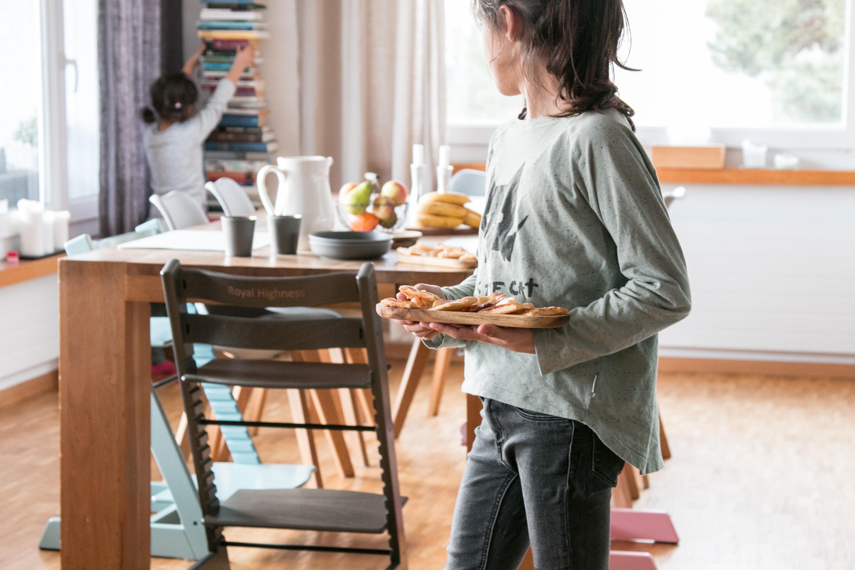 Zwei Kinder vor einem Tisch, der mit einem Zvieri gedeckt ist. Das hintere Kind schaut sich das Bücherregal an, das vordere Kind dreht sich zu ihm hin.