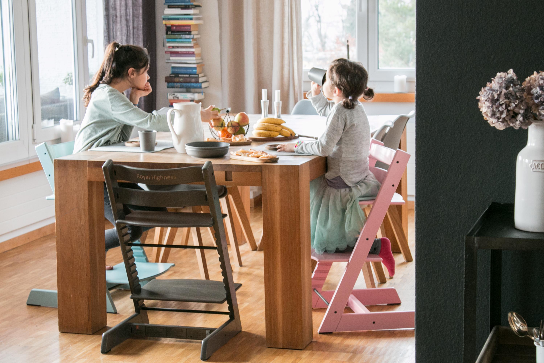 Zwei Kinder sitzen auf ihren TrippTrapps am Tisch.